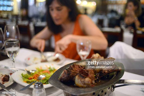 A woman eats meat at a traditional grill restaurant in Buenos Aires on October 27 2015 Sausages ham and other processed meats cause bowel cancer and...