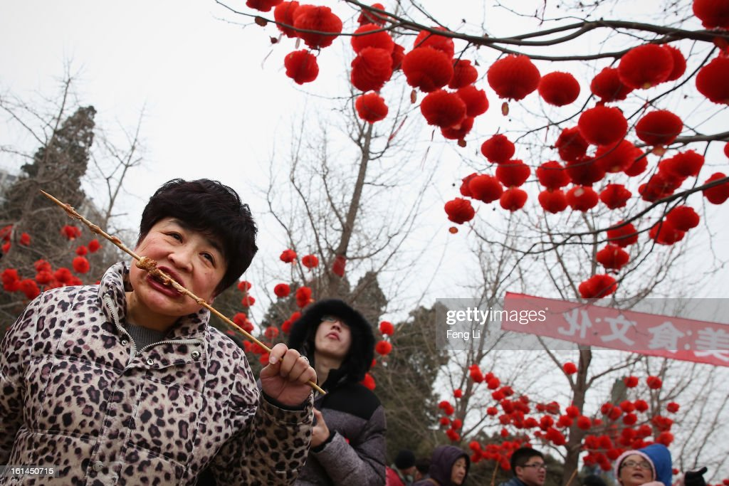 A woman eats mutton skewer at a Spring Festival Temple Fair for celebrating Chinese Lunar New Year of Snake on February 11, 2013 in Beijing, China. The Chinese Lunar New Year of Snake also known as the Spring Festival, which is based on the Lunisolar Chinese calendar, is celebrated from the first day of the first month of the lunar year and ends with Lantern Festival on the Fifteenth day.