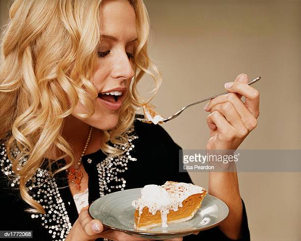 Woman Eats Pumpkin Pie With a Spoon From a Plate