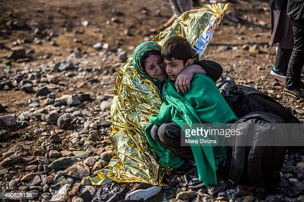 A woman embraces a boy as they arrive with other refugees on the shores of the Greek island of Lesbos after crossing the Aegean sea from Turkey on a...