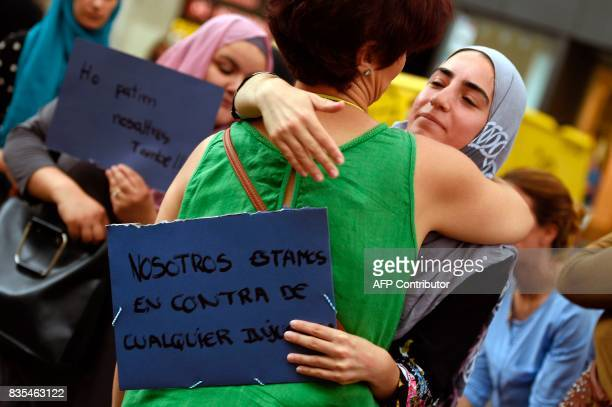 A woman embraces a Muslim resident of Barcelona holding a placard reading 'We are against any injustice' as they demonstrate on the Las Ramblas...