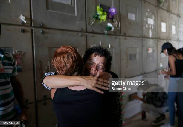 A woman embraces Ana Ruiz at the end of her husband's funeral service in front of the mausoleum plot where Victor Ruiz Ramos was interred in Corozal...
