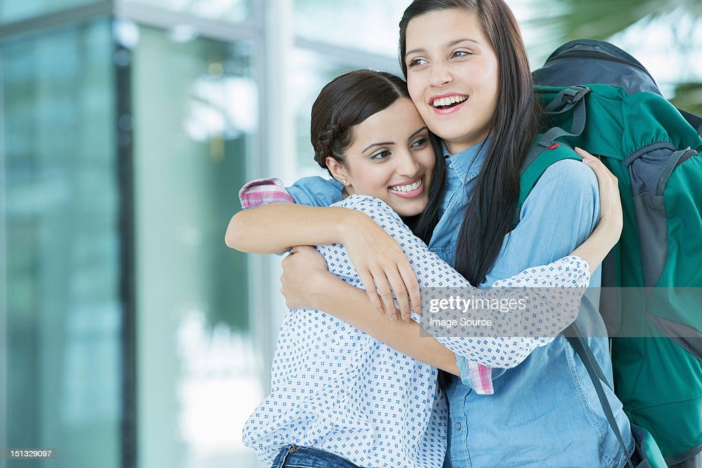 Woman embracing friend with backpack : Stock Photo