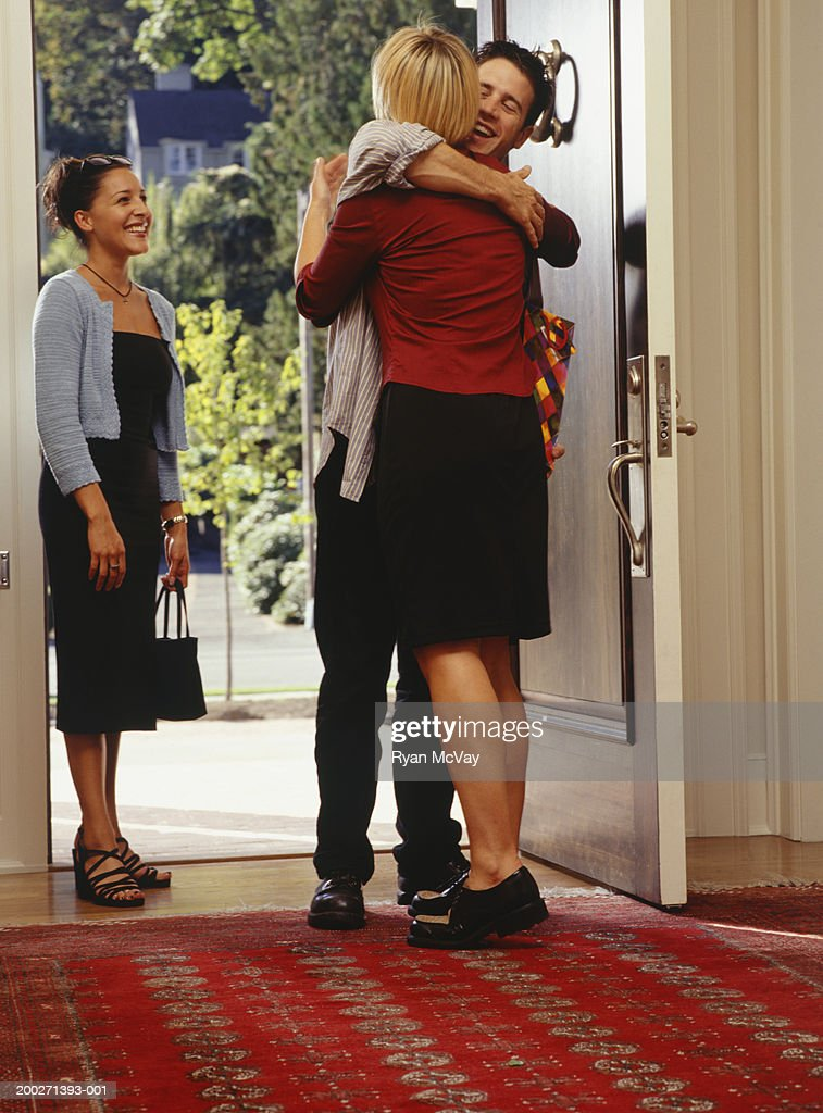 Woman embracing friends at front door of home