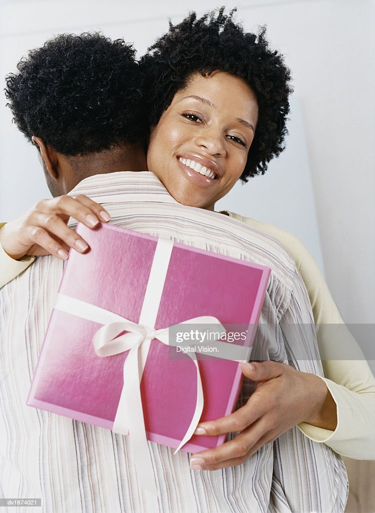 Woman Embracing Her Partner, Holding a Gift : Stock Photo