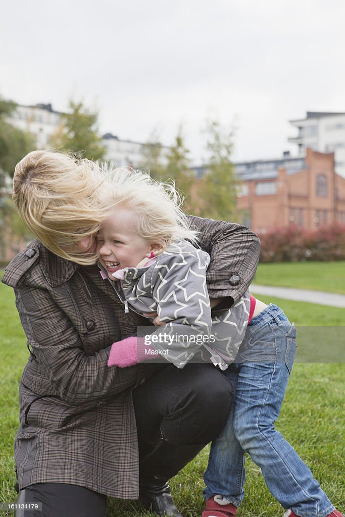 Woman embracing her smiling daughter (2-3) : Stock Photo