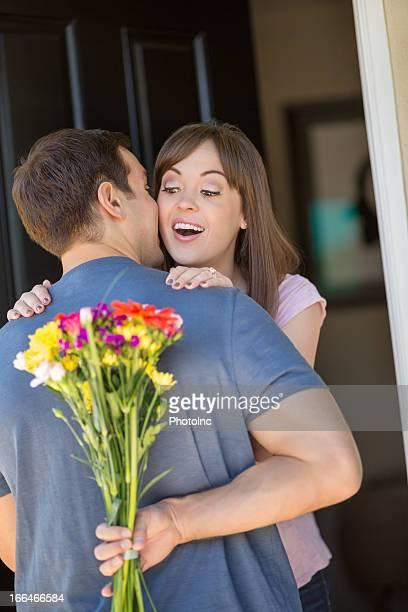 Woman Embracing Man As He Hides Bouquet