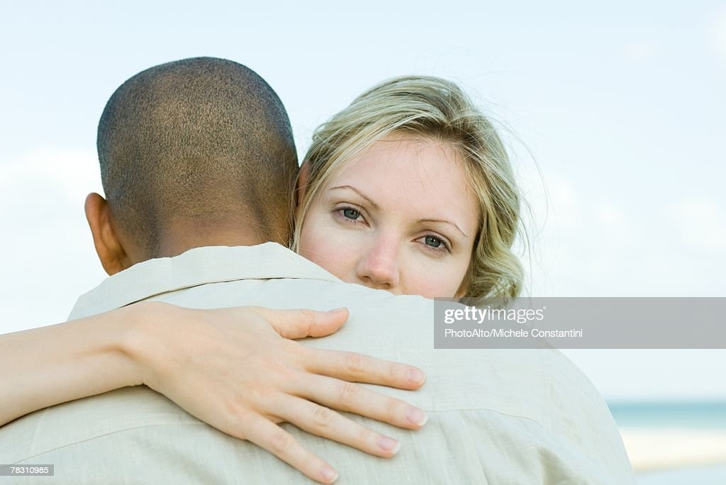 Woman embracing man, looking over his shoulder at camera : Stock Photo