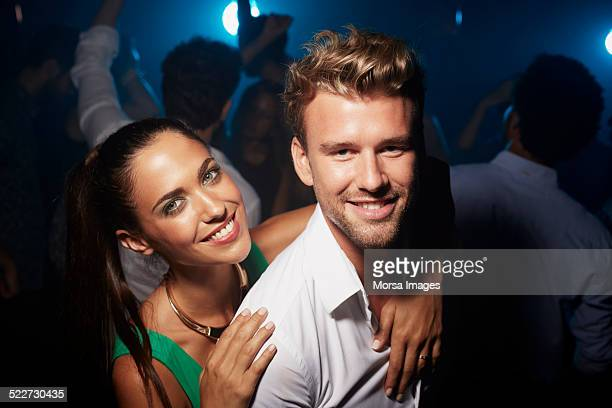 Woman embracing man on dance floor in nightclub