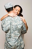 Woman embracing soldier in fatigues
