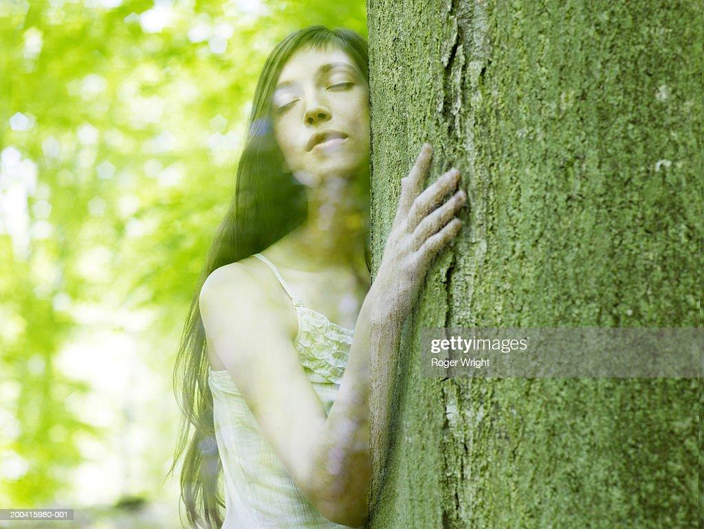 Woman embracing tree, eyes closed (digital composite)