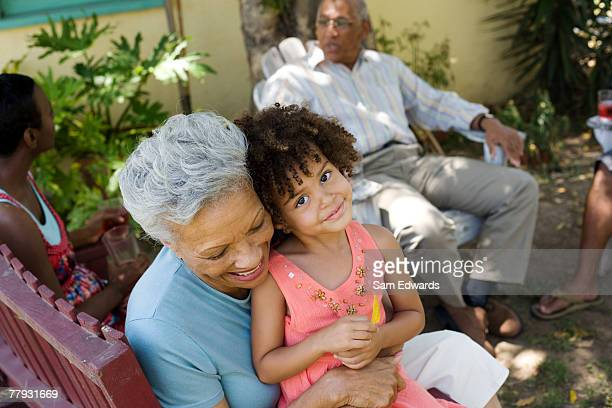 Woman embracing young girl with people in background