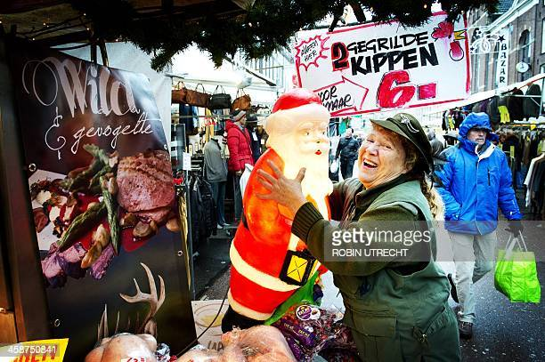 A woman embrasses a plastic Santa Claus figure at the Albert Cuypmarkt in Amsterdam during the last weekend before Christmas in the Netherlands on...