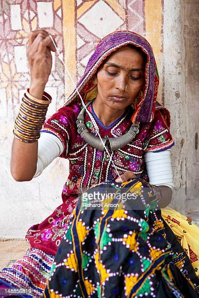 Woman embroidering fabric outside house.