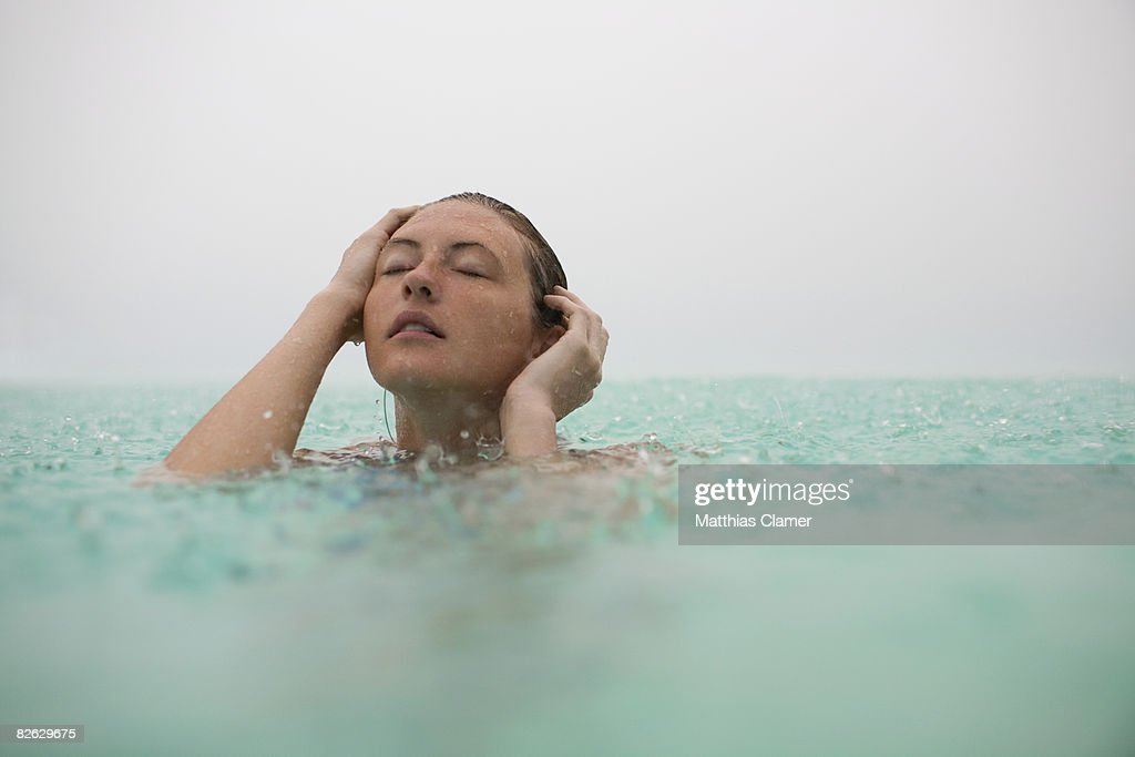 woman emergers from water while it rains : Stock Photo