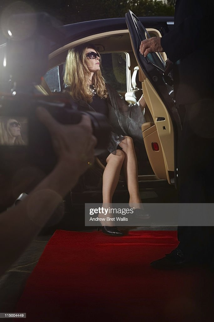 Woman emerging from limousine onto red carpet : Stock Photo