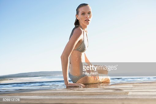 Woman emerging from swimming pool : Stock-Foto