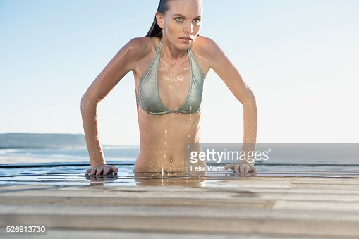 Woman emerging from swimming pool : Bildbanksbilder