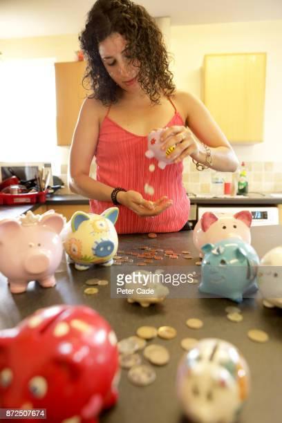 Woman emptying piggy banks
