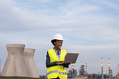 Woman engineer checking the data of the oil refinery, using a laptop computer.