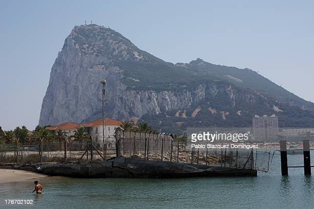 A woman enjoy the beach next to the border fence while people are seen at a Gibraltar's beach on August 17 2013 in Linea de la Concepcion Spain...