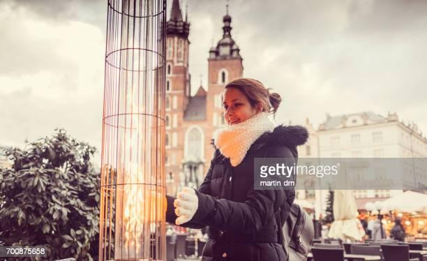 Woman enjoying a patio heater in Krakow