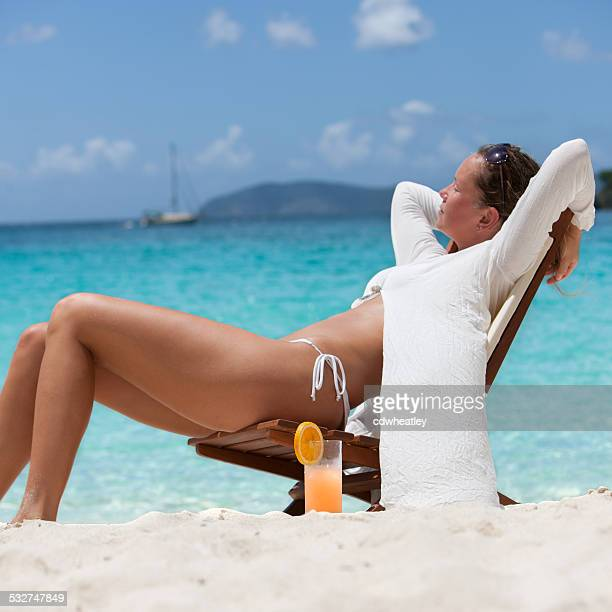 woman enjoying a tropical cocktail at the Caribbean beach