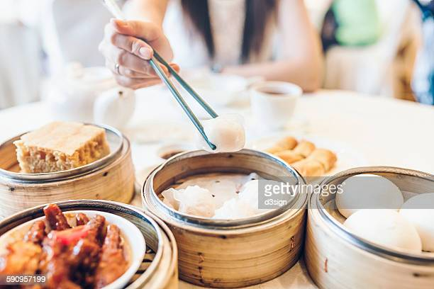 Woman enjoying a variety of dim sum in restaurant