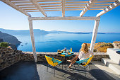 Woman enjoying breakfast with beautiful view over Santorini