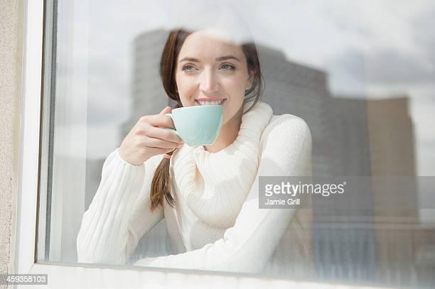 Woman enjoying coffee looking out window