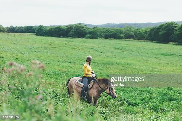 Woman enjoying horse riding, Hokkaido