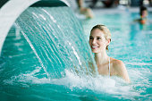 Woman enjoying hydrotherapy and water stream in spa pool