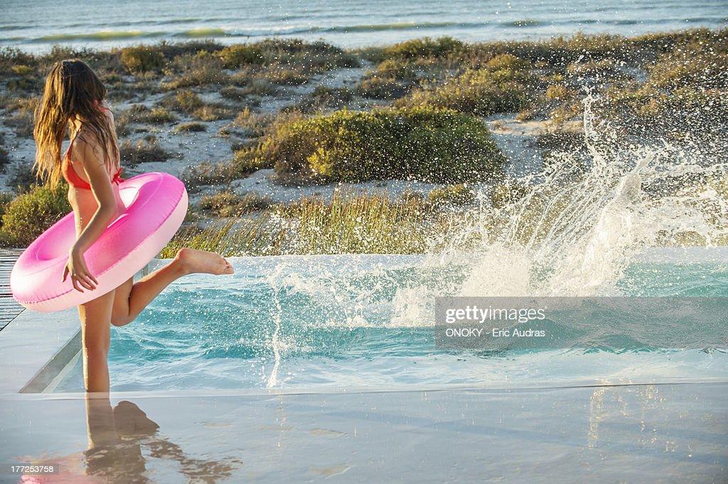 Woman enjoying in a swimming pool on the beach : Stock Photo