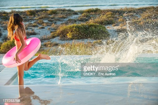 Woman enjoying in a swimming pool on the beach : Stock Photo