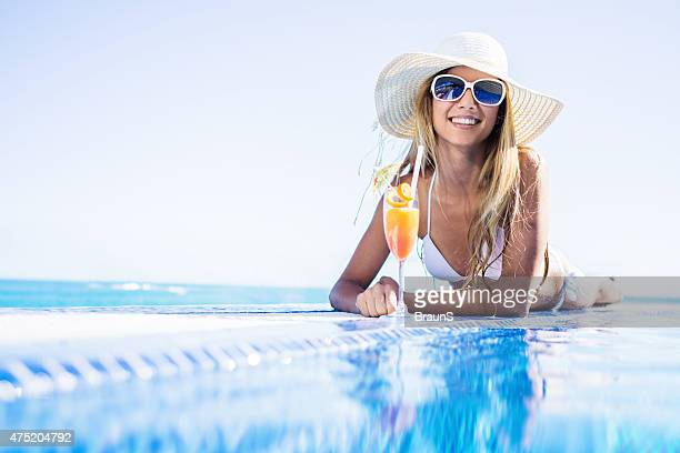 Woman enjoying in summer cocktail at the pool.