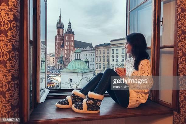 Mulher a gostar de cidade de Cracóvia da janela