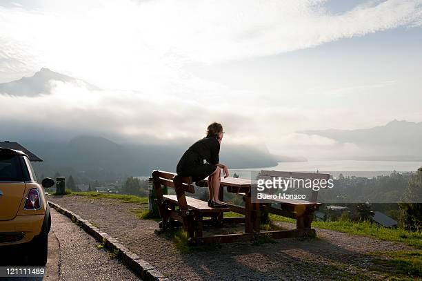 woman enjoying landscape sitting on bench, lake