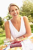 Woman Enjoying Meal In Garden