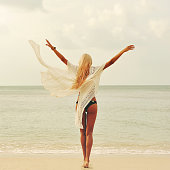 Happy woman enjoying nature at the beach. Arms wide open, freedom