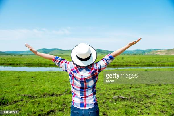 Woman enjoying nature with arms raised