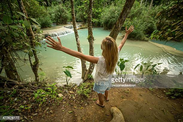 Woman enjoying nature-Arms outstretched near waterfalls