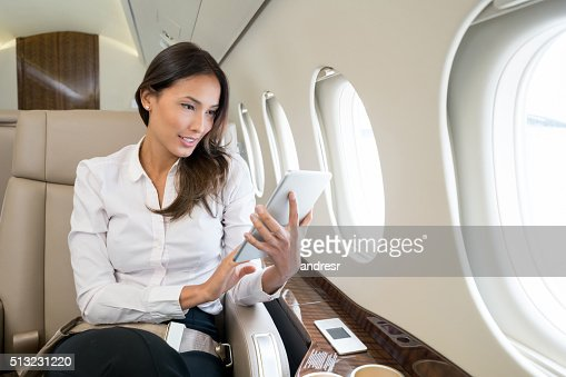 Woman enjoying onboard entertainment in her tablet computer