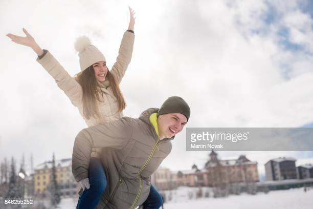 Woman enjoying piggyback ride, arms outstretched.