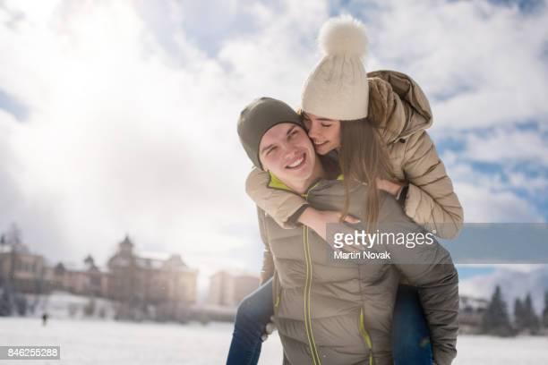 Woman enjoying piggyback ride on snowy winter day