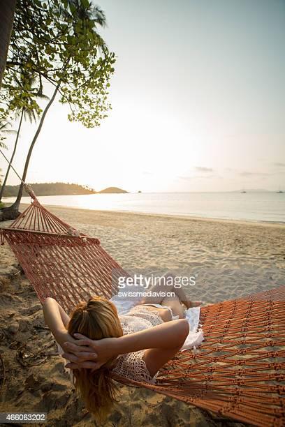 Woman enjoying sunset from hammock