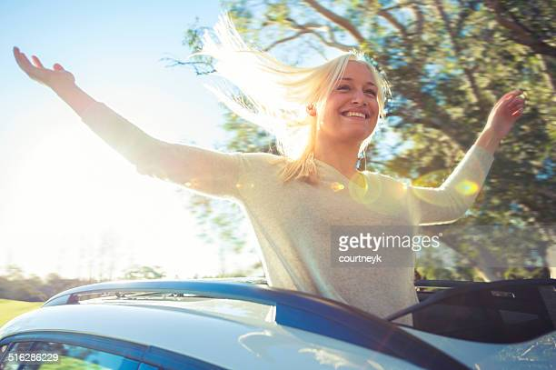 Woman enjoying the freedom of a sun roof