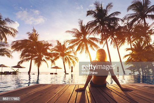 Woman enjoying vacation holidays luxurious beachfront hotel resort swimming pool : Foto de stock