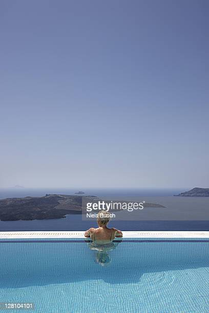 Woman enjoying view at the edge of infinity pool