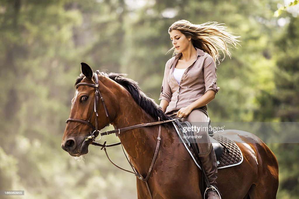 Woman enjoying while horseback riding.