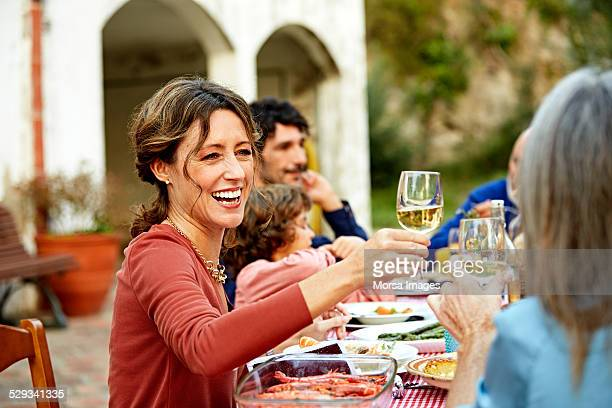 Woman enjoying wine while having meal with family